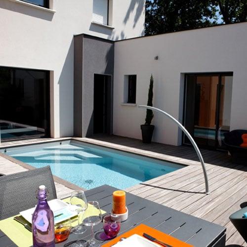 Implantée dans une cour, la piscine est une véritable pièce de la maison. Réalisation Caron Piscines.