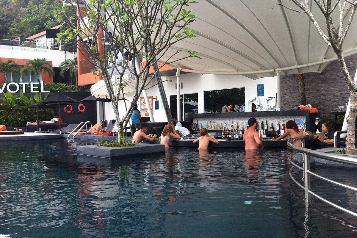 Une longue banquette sinueuse suit la courbe du bassin, et fait place à un bar arrondi avec tabourets immergés.