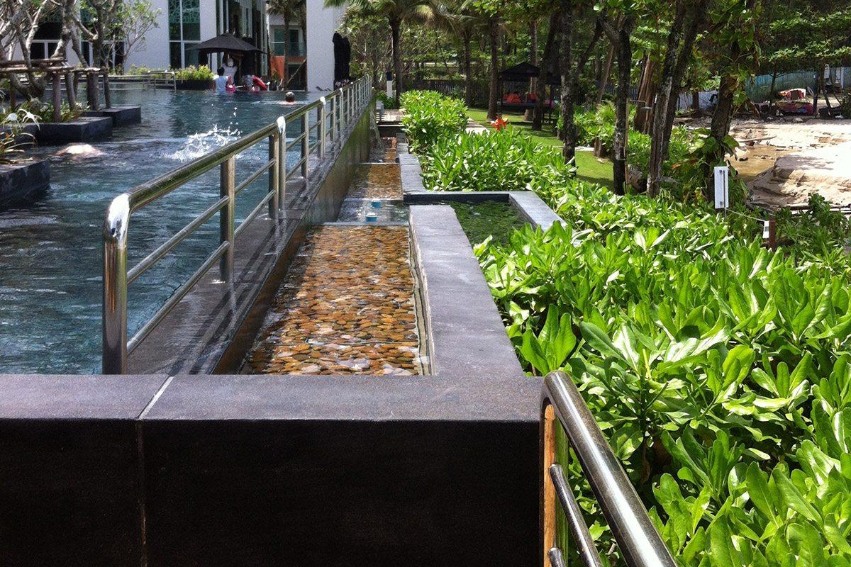 Les bacs de débordement installés à différentes hauteurs sont décorés de galets bruns.