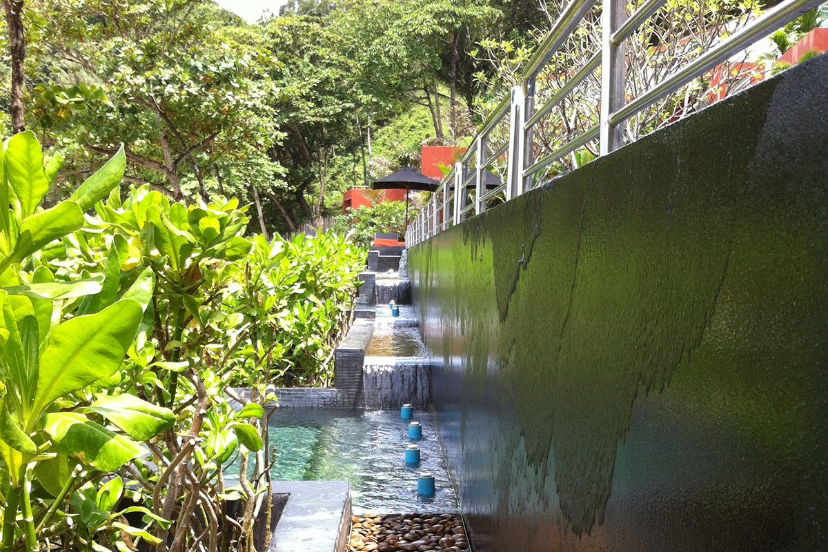 Le long mur rectiligne de débordement affiche une couleur qui tranche avec les teintes de la végétation et de la plage.