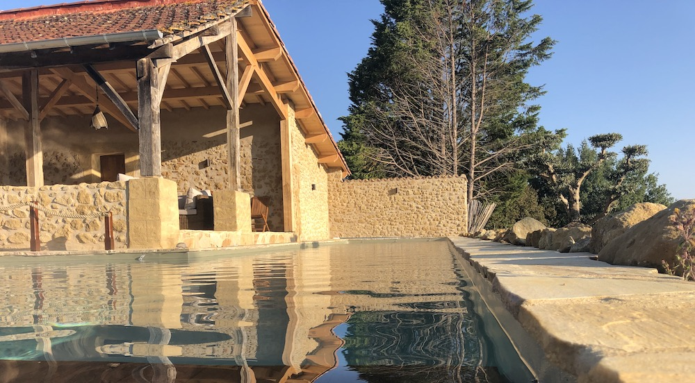 La pierre de Dordogne irrégulière posée en margelle ajoute au charme intemporel de la réalisation.