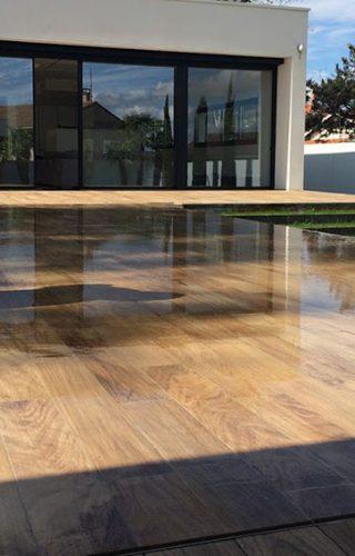 Les lames larges du plancher renforcent l'esprit contemporain et dépouillé de la piscine. Réalisation Azenco